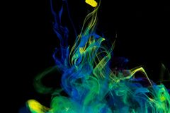 Color paint drops in water. Ink swirling underwater. Cloud of silky ink collision on black background. Colorful abstract smoke explosion animation. Close up royalty free stock images