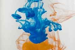 Color paint drops in water. Ink swirling underwater. Royalty Free Stock Images