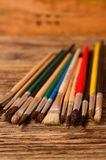 Color paintbrushes on vertical photo placed on wooden board Royalty Free Stock Photo