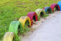 Color painted tires in a kids park. Separating grass from concrete Stock Photography