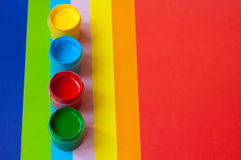 Color paints. Open bright color paint tins standing on paper sheet of different color. Main focus on green tin Stock Image