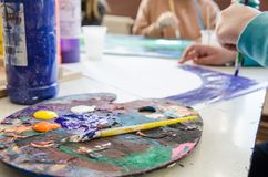 Color palette and a brush in foreground with students painting in class out-of-focus in the background. Color palette and a brush are in foreground and the stock images