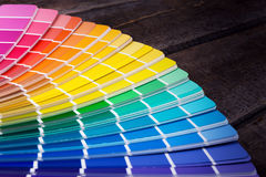 Color palette guide of paint samples catalog. On old wooden table royalty free stock photo