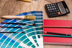 Color palette, pencil, calculator and notepad on. Desk Royalty Free Stock Image