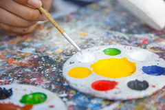 Color on pallete and paintbrush on dirty table Stock Photography