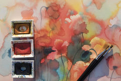 Color pans with brushes on poppies watercolor background Stock Photo