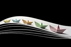 5 Paper colorful boats on waves on a black background. A team of five color paper boats in the dynamics on the waves and on a black background. 5 ships of royalty free stock image