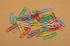 Color paper clips on brown paper background Royalty Free Stock Photography