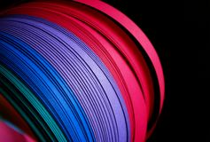 Color paper strips. Close up, contrasting black background. Magenta, purple and blue are the main colors royalty free stock photo