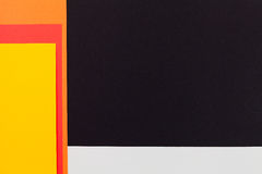 Color papers background. Color papers geometry flat composition background with black yellow orange red and grey tones Stock Photography