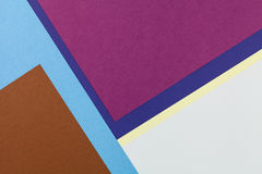 Color papers background. Color papers geometry flat composition background with brown blue purple grey and yellow tones Royalty Free Stock Photography