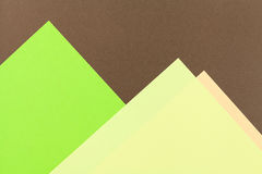Color papers background. Color papers geometry flat composition background with green and brown tones Stock Images