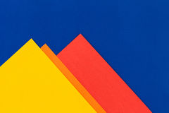 Color papers background. Color papers geometry flat composition background with yellow orange red and blue tones Stock Images