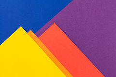 Color papers background. Color papers geometry flat composition background with yellow orange red violet and blue tones Stock Photos