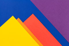 Color papers background. Color papers geometry flat composition background with yellow orange red violet and blue tones Royalty Free Stock Photos