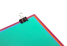 Color papers and black clip. Royalty Free Stock Images