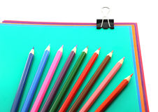 Color papers, black clip and color pencils Royalty Free Stock Images