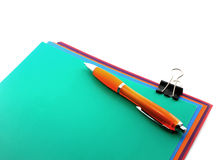 Color papers, black clip and orange pen Royalty Free Stock Photography
