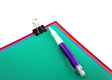 Color papers, black clip and pen Royalty Free Stock Photography
