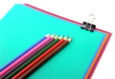 Color papers, black clip and pencils Stock Photos