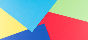 Color papers geometry flat composition background with yellow, green, red and blue tones. Color papers geometry flat composition background with yellow, greenery stock photography