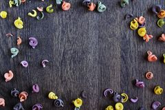 Color pasta scattered on wooden table stock photo
