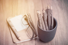 Color pencil made of branches with glasses and note book on wood Royalty Free Stock Photo