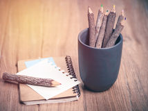 Color pencil made of branches with glasses and note book on wood Stock Images