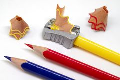 Color pencil and prism sharpener macro photo on white background. Drawing as hobby banner template. Sharpening pencils concept. Yellow, red and blue crayons royalty free stock photos