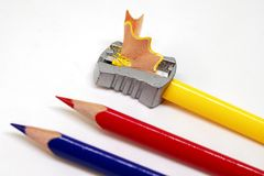 Color pencil and prism sharpener macro photo on white background. Sharpening pencils concept. Drawing as hobby banner template. Yellow, red and blue crayons stock photography
