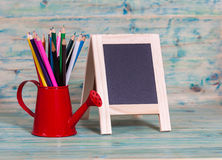 Color pencil in red watering can and  blackboard Royalty Free Stock Photography