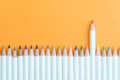Color pencil in row with stand out pink one using as individual creativity, leadership or feminine and woman leader idea royalty free stock photos