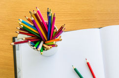 Color pencil and sketchbook on wood table Royalty Free Stock Images