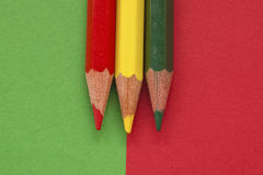 Color pencils. Green, yellow and red color pencil isolated in green and red background Stock Photos