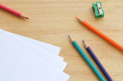 Color pencils. With sharpener and some sheets, on a desk Stock Photography