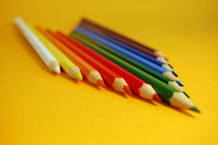 Color Pencils. Arrow made of color pencils on a yellow background Stock Photo