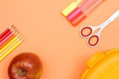 Color pencils, apple, felt pens, scissors and lunch box. School. School supplies. Color pencils, red apple, felt pens, scissors and lunch box on pink background royalty free stock photos