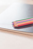 Color pencils on black notebook Royalty Free Stock Images