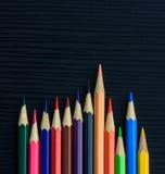Color pencils on black wood Stock Photos
