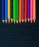 Color pencils on black wood Stock Photo