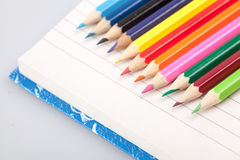 Color pencils on a blank notebook Royalty Free Stock Photo