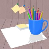 Color pencils in blue mug. With white paper on wood background Royalty Free Stock Photo