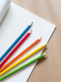 Color pencils with a book on brown background. Color pencils with a  book, blank page on brown background Stock Images