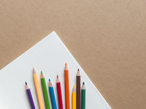 Color pencils with a book on brown background. Color pencils with a  book, blank page on brown background Stock Photos