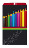 Color pencils in the box. Several color pencils in a box decorated with floral ornaments. A black box is isolated against white background Royalty Free Stock Photography