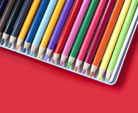 Color pencils in a box on a red background Stock Photos