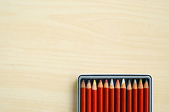 Color pencils in box on wood background Royalty Free Stock Photo