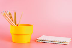 Color pencils in bucket with notebook on pink Stock Images