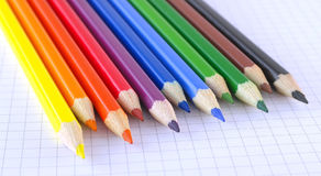 Color pencils on the checked paper of notepad Stock Photography