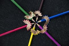 Color pencils circle facing each other. In a black textured background with sharpened rubish stock photo